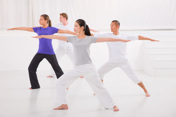 Sporty people stretching hands yoga class in fitness studio