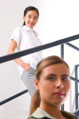 Smiling asian young woman standing staircase