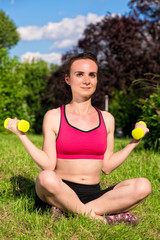 Young woman exercising with dumbbells in nature