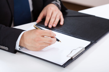 Hands of businessman writing on clipboard