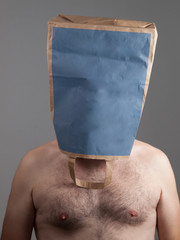 Nude Man with his face hidden in a paper bag