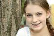Teenager mit Brackets lehnt an Baum
