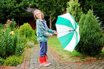 Kid girl with umbrella in raincoat and boots