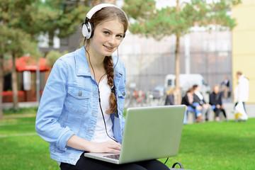 Teenager arbeitet mit Laptop im Park