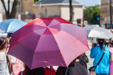 Menschen mit Sonnenschirmen in der Stadt