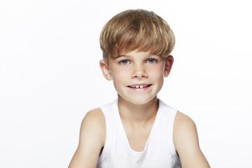 Portrait of young boy in vest, studio.