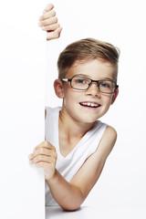 Portrait of young boy wearing glasses, studio.