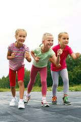 Three schoolgirls are at the start on the treadmill