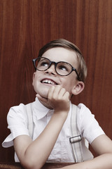 Young boy in glasses, looking up.