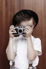 Young boy taking photograph with old camera.