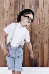 Young boy in shirt and braces posing, studio.