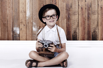 Young boy sitting on floor with camera.