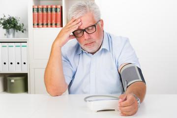 besorgter mann prüft seinen blutdruck
