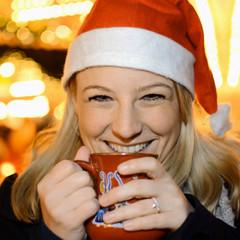 Twen mit Nikolaus-Mütze trinkt Punsch