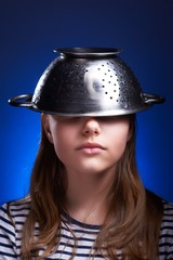Teen girl with a colander on her head