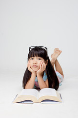 Portrait of boring little Asian child reading a book