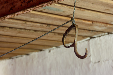 Old rusty meat hook hanging on a rope