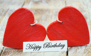Happy birthday card with two red wooden hearts
