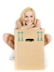 Young woman rests on her moving box