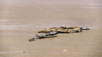 Convoy of bamboo move slowly on the mekong river