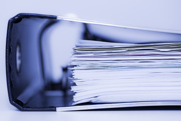 Toned image of binder with documents.