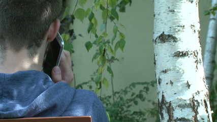 Eco concept - teenager charging smartphone from tree