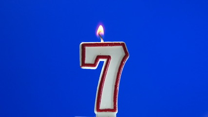 Number 7 - seven birthday candle burning