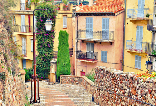 Street with buildings and paved brick walkway in Cannes, France - 69053322