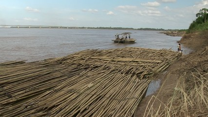 Boat leaving from group of bamboo raft along the mekong river