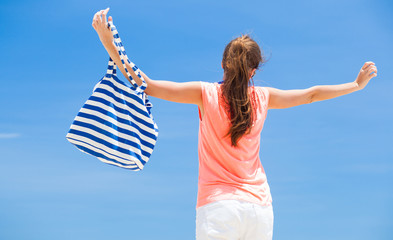 back view of a fit young woman with stripy bag at tropical beach