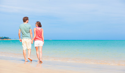back view of couple walking at tropical beach