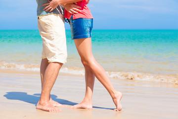 couple kissing at beach. legs view