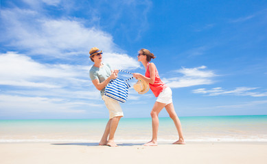 front view of happy young couple running at tropical beach
