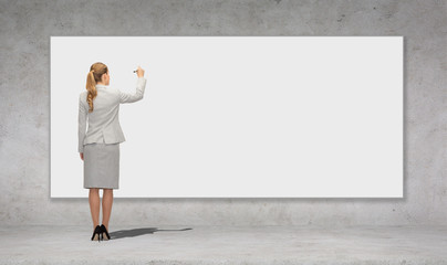 businesswoman writing with marker on white board