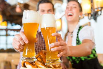 Bayrisches Paar stößt mit Bier an