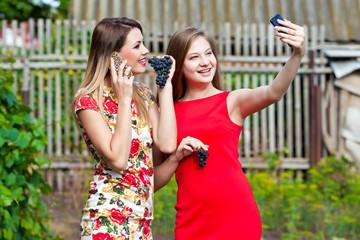 Две девушки с сотовым телефоном в руках