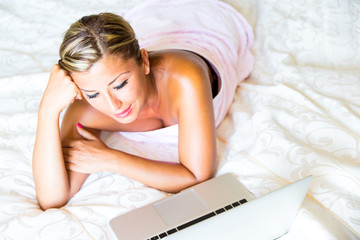 Woman in bedroom chats on laptop