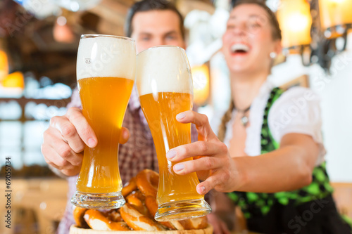 Bayrisches Paar stößt mit Bier an - 69055734
