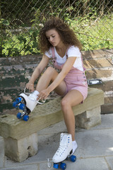 Teenage girl fastening laces on her roller skates