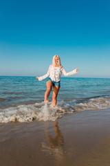Schöne Frau spielt mit Wasser am Strand auf Kreta