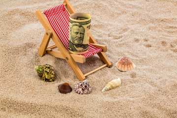 Liegestuhl mit Sparschwein und Dollar