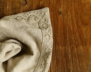 old wooden background with gray linen lace napkin