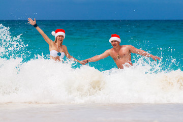 Young beautiful couple in love having fun in the waves dressed i