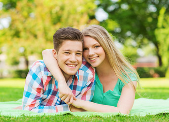 smiling couple lying on blanket in park