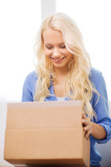 smiling woman opening cardboard box at home