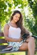 Girl on bench in park with ereader