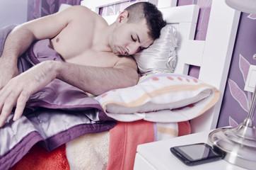 sleeping young man near to smartphone