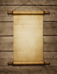 Old grunge blank paper scroll at the wooden wall