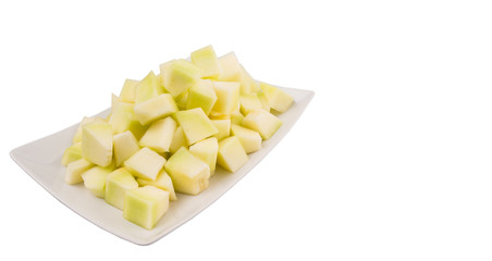 Bite sized honeydew pieces on white plate