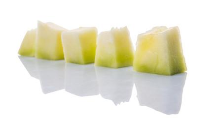 Bite sized honeydew pieces over white background